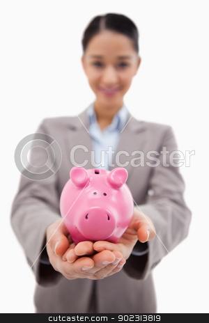 Portrait of a happy businesswoman showing a piggy bank stock photo, Portrait of a happy businesswoman showing a piggy bank against a white background by Wavebreak Media