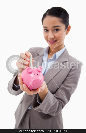Portrait of a businesswoman putting a bank note in a piggy bank stock photo, Portrait of a businesswoman putting a bank note in a piggy bank against a white background by Wavebreak Media