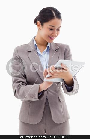 Portrait of a businesswoman using a tablet computer stock photo, Portrait of a businesswoman using a tablet computer against a white background by Wavebreak Media