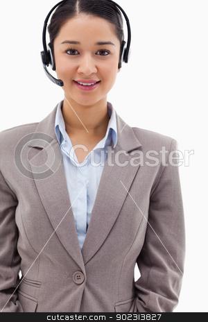 Portrait of a brunette operator posing with a headset stock photo, Portrait of a brunette operator posing with a headset against a white background by Wavebreak Media