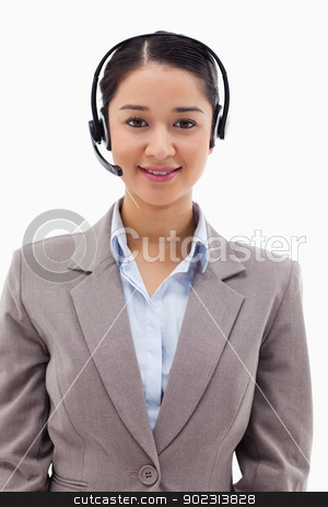 Portrait of a smiling operator posing with a headset stock photo, Portrait of a smiling operator posing with a headset against a white background by Wavebreak Media