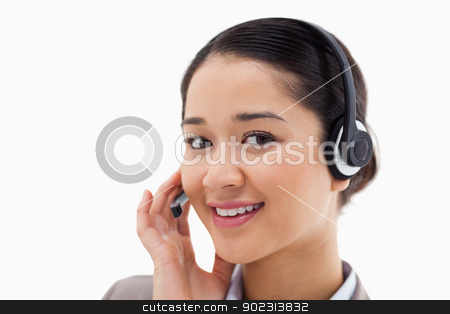Close up of a smiling operator posing with a headset stock photo, Close up of a smiling operator posing with a headset against a white background by Wavebreak Media