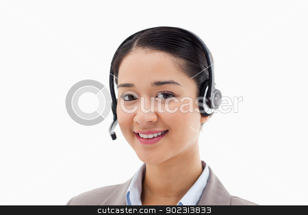 Smiling operator posing with a headset stock photo, Smiling operator posing with a headset against a white background by Wavebreak Media