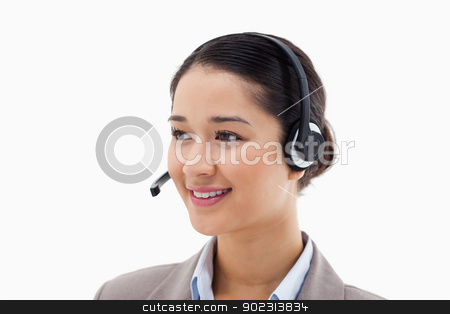 Happy operator posing with a headset stock photo, Happy operator posing with a headset against a white background by Wavebreak Media
