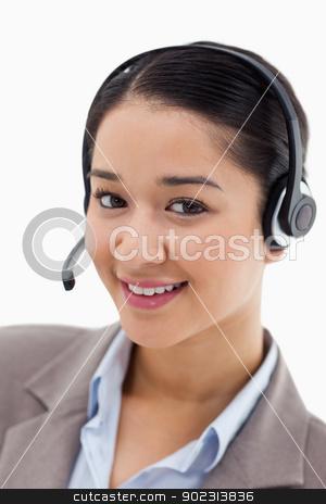Portrait of a happy office worker posing with a headset stock photo, Portrait of a happy office worker posing with a headset against a white background by Wavebreak Media
