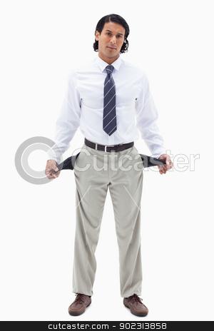 Portrait of a broke businessman showing his empty pockets stock photo, Portrait of a broke businessman showing his empty pockets against a white background by Wavebreak Media