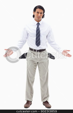 Portrait of an innocent businessman showing his empty pockets stock photo, Portrait of an innocent businessman showing his empty pockets against a white background by Wavebreak Media