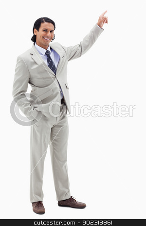 Portrait of a smiling businessman pointing at a copy space stock photo, Portrait of a smiling businessman pointing at a copy space against a white background by Wavebreak Media