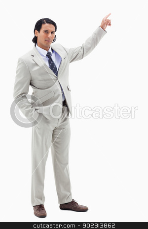 Portrait of a serious businessman pointing at a copy space stock photo, Portrait of a serious businessman pointing at a copy space against a white background by Wavebreak Media