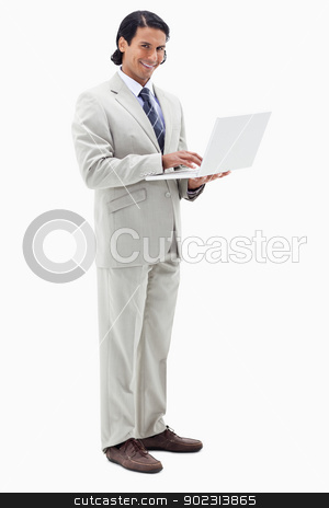 Portrait of a smiling businessman using a notebook stock photo, Portrait of a smiling businessman using a notebook against a white background by Wavebreak Media
