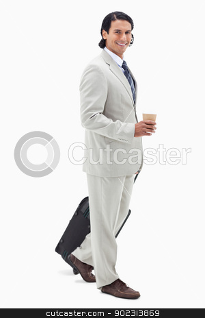 Side view of businessman with coffee and wheely bag stock photo, Side view of businessman with coffee and wheely bag against a white background by Wavebreak Media