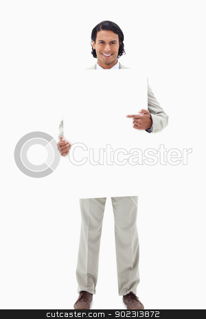 Businessman pointing at blank sign in his hands stock photo, Businessman pointing at blank sign in his hands against a white background by Wavebreak Media