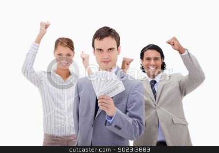 Businessman with cheering colleagues and money stock photo, Businessman with cheering colleagues and money against a white background by Wavebreak Media