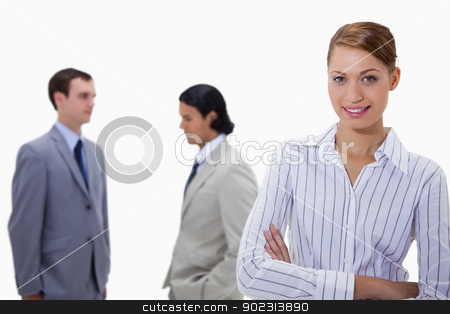 Busiensswoman with arms folded and talking colleagues behind her stock photo, Businesswoman with arms folded and talking colleagues behind her against a white background by Wavebreak Media