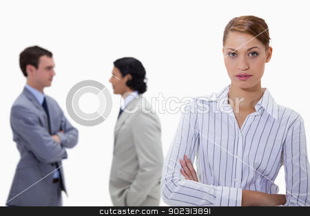 Businesswoman with talking colleagues behind her stock photo, Businesswoman with talking colleagues behind her against a white background by Wavebreak Media
