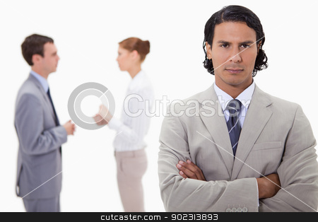 Serious businessman with talking colleagues behind him stock photo, Serious businessman with talking colleagues behind him against a white background by Wavebreak Media