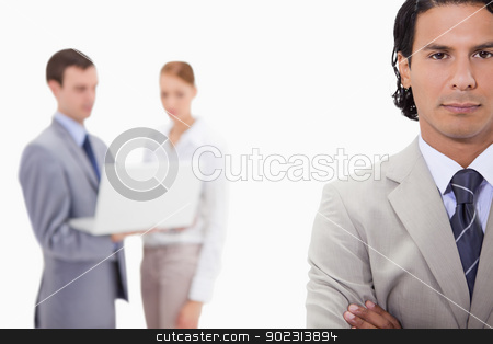 Businessman with colleagues with laptop behind him stock photo, Businessman with colleagues with laptop behind him against a white background by Wavebreak Media