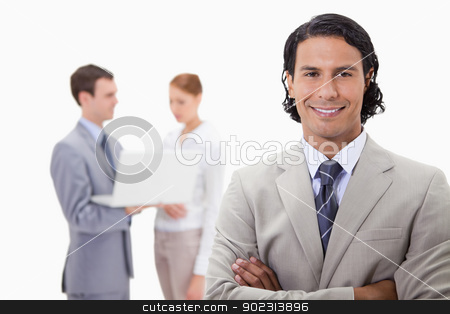 Smiling businessman with colleagues working on laptop behind him stock photo, Smiling businessman with colleagues working on laptop behind him against a white background by Wavebreak Media
