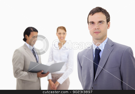 Young businessman with colleagues behind him stock photo, Young businessman with colleagues behind him against a white background by Wavebreak Media