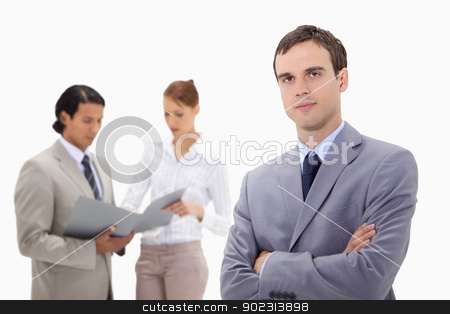 Young businessman with talking colleagues behind him stock photo, Young businessman with talking colleagues behind him against a white background by Wavebreak Media