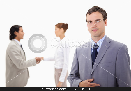 Businessman with hand shaking colleagues behind him stock photo, Businessman with hand shaking colleagues behind him against a white background by Wavebreak Media