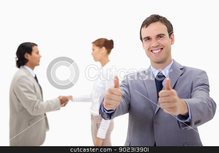 Businessman approving with hand shaking colleagues behind him stock photo, Businessman approving with hand shaking colleagues behind him against a white background by Wavebreak Media