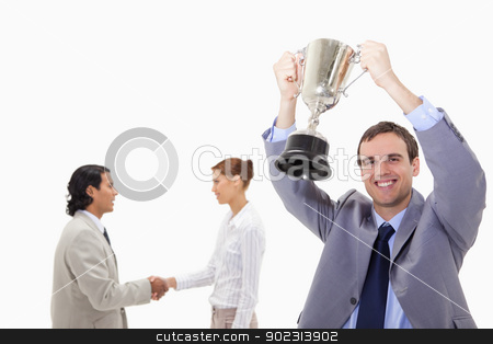 Businessman raising cup with hand shaking colleagues behind him stock photo, Businessman raising cup with hand shaking colleagues behind him against a white background by Wavebreak Media