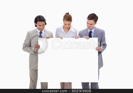 Businessteam looking at blank sign in their hands stock photo, Businessteam looking at blank sign in their hands against a white background by Wavebreak Media