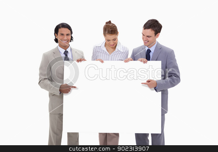 Businessteam pointing at blank sign in their hands stock photo, Businessteam pointing at blank sign in their hands against a white background by Wavebreak Media
