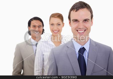 Smiling businessteam lined up stock photo, Smiling businessteam lined up against a white background by Wavebreak Media