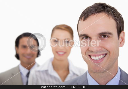Smiling businessteam standing in a row stock photo, Smiling businessteam standing in a row against a white background by Wavebreak Media