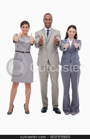 Smiling businessteam giving thumbs up stock photo, Smiling businessteam giving thumbs up against a white background by Wavebreak Media