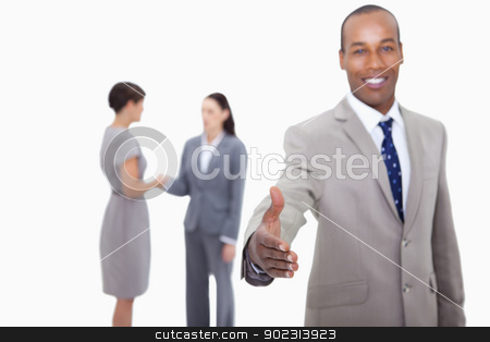 Smiling businessman offering his hand with hand shaking colleagu stock photo, Smiling businessman offering his hand with hand shaking colleagues behind him against a white background by Wavebreak Media
