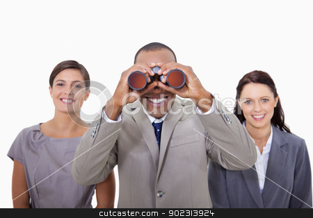Businessman with colleagues looking through binoculars stock photo, Businessman with colleagues looking through binoculars against a white background by Wavebreak Media