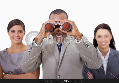 Smiling businessman with colleagues looking through binoculars stock photo, Smiling businessman with colleagues looking through binoculars against a white background by Wavebreak Media