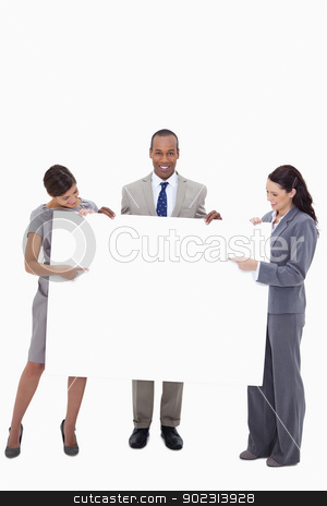 Businesspeople pointing at blank sign in their hands stock photo, Businesspeople pointing at blank sign in their hands against a white background by Wavebreak Media