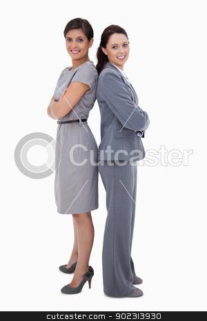Businesswomen standing back on back stock photo, Businesswomen standing back on back against a white background by Wavebreak Media