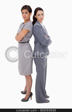 Serious businesswomen standing back on back stock photo, Serious businesswomen standing back on back against a white background by Wavebreak Media