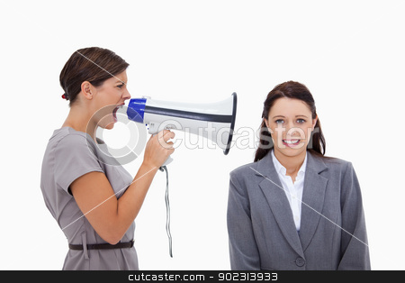 Businesswoman using megaphone to yell at colleague stock photo, Businesswoman using megaphone to yell at colleague against a white background by Wavebreak Media