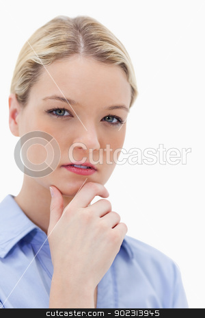 Thoughtful woman touching her chin stock photo, Thoughtful woman touching her chin against a white background by Wavebreak Media