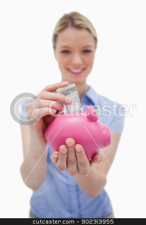 Money being put into piggy bank by woman stock photo, Money being put into piggy bank by woman against a white background by Wavebreak Media
