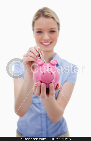 Note being put into piggy bank by woman stock photo, Note being put into piggy bank by woman against a white background by Wavebreak Media