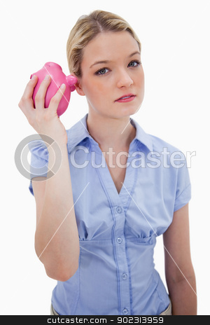 Woman curiously shaking her piggy bank stock photo, Woman curiously shaking her piggy bank against a white background by Wavebreak Media