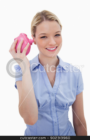 Smiling woman shaking her piggy bank stock photo, Smiling woman shaking her piggy bank against a white background by Wavebreak Media