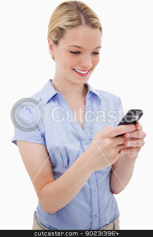 Smiling woman writing text message stock photo, Smiling woman writing text message against a white background by Wavebreak Media