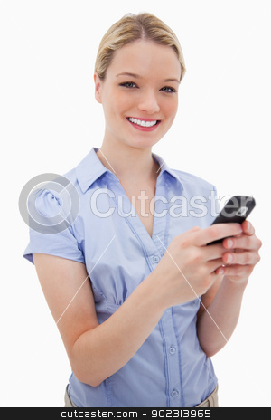 Smiling woman holding her cellphone stock photo, Smiling woman holding her cellphone against a white background by Wavebreak Media