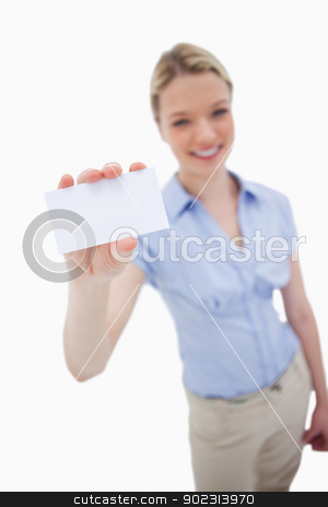 Blank business card being held by smiling woman stock photo, Blank business card being held by smiling woman against a white background by Wavebreak Media