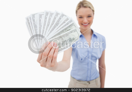 Money being held by smiling woman stock photo, Money being held by smiling woman against a white background by Wavebreak Media