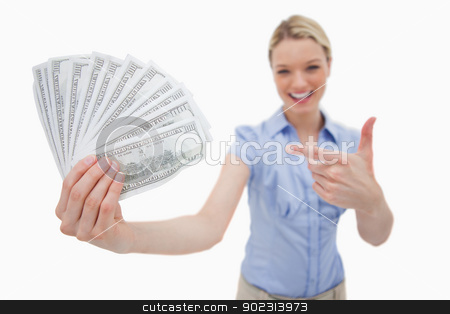 Money being held and pointed at by woman stock photo, Money being held and pointed at by woman against a white background by Wavebreak Media