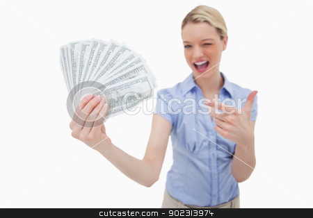 Woman holding money and pointing at it stock photo, Woman holding money and pointing at it against a white background by Wavebreak Media